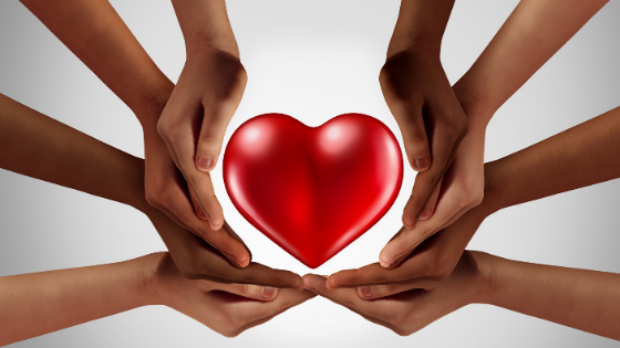 Hands around a heart signifying charity.