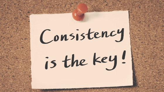 "A sign on a cork board ""Consistency is Key"""